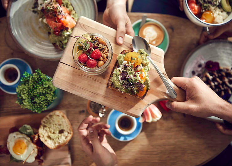 someone passing brekkie board to friend across the table, with avo smash and coffees on table.