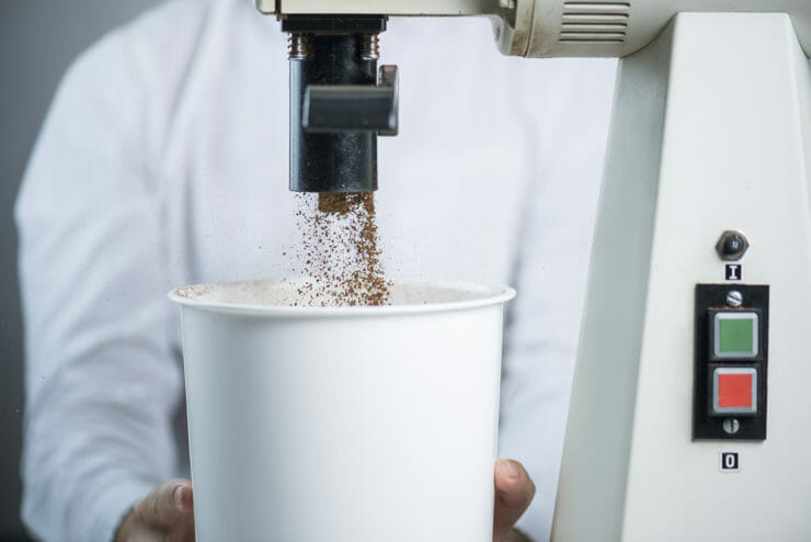 grinder grinding coffee into a white bucket.