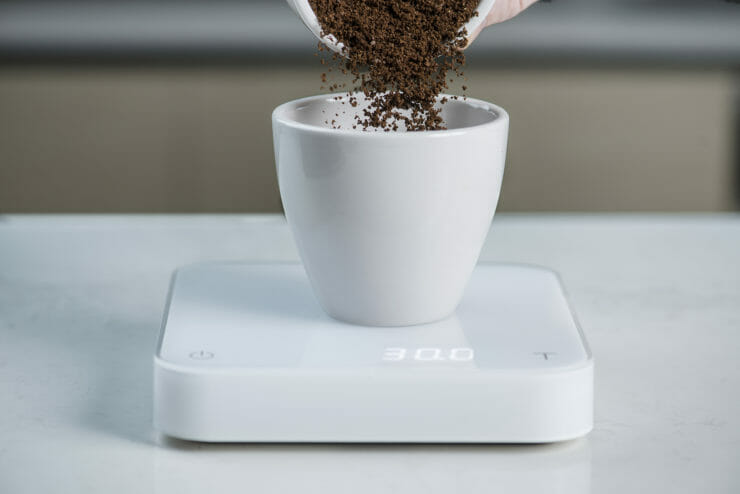coffee grinds being poured into coffee cup on scale.