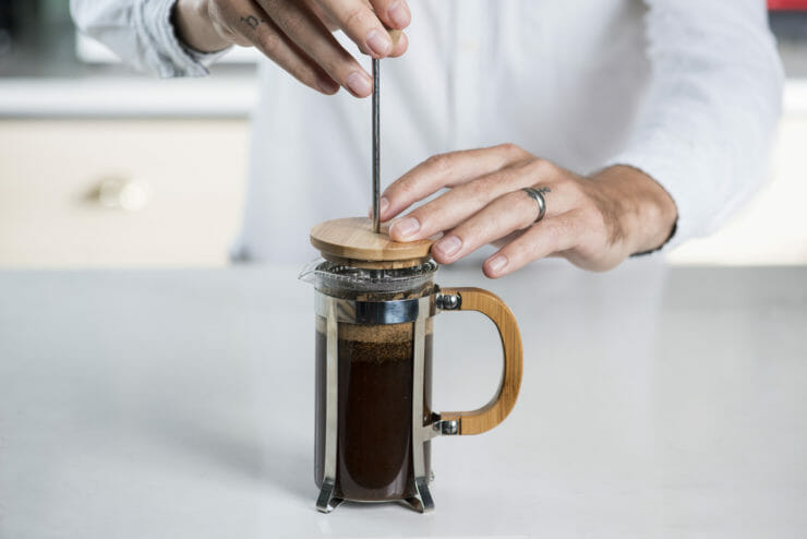 someone pressing the french press down.