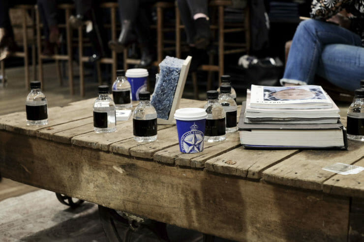 low wooden table in rag and bone with bluestone lane cups on it.